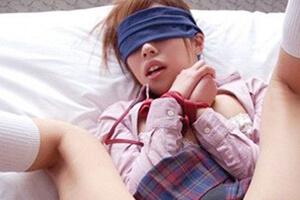 女子高生の格好で目隠しをして手首を縛っている若いギャル風の女性